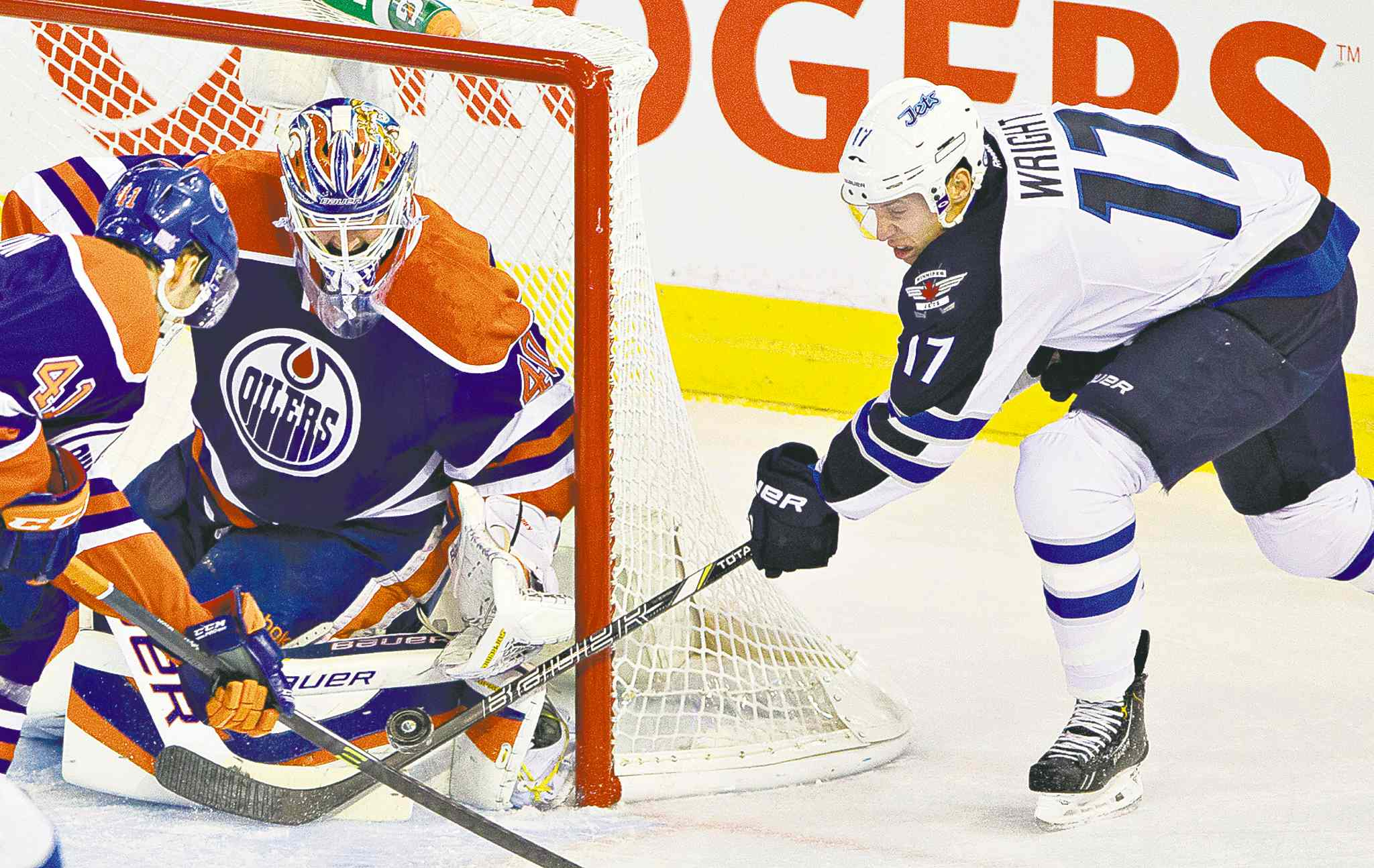 Winnipeg forward James Wright is denied by Edmonton goalie Devan Dubnyk and forward Will Acton during first-period action Tuesday night.