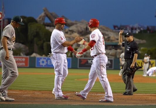 Los Angeles Angels' Albert Pujols, second from left, and Mike Trout, second from right, congratulate each other after scoring on a single by David Freese as Oakland Athletics starting pitcher Kendall Graveman, left, walks away and home plate umpire Mark Wegner makes the call during the first inning of a baseball game, Monday, April 20, 2015, in Los Angeles. (AP Photo/Mark J. Terrill)