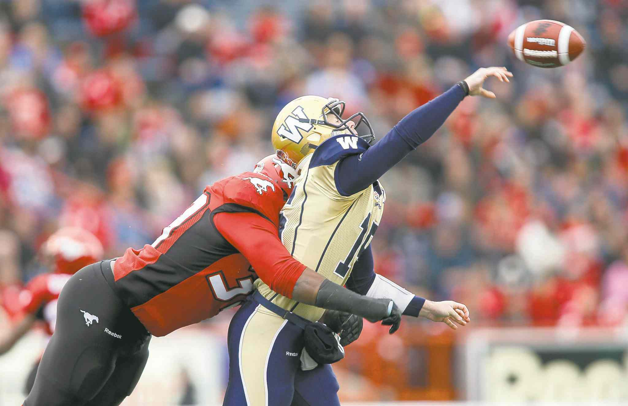 Blue Bombers' quarterback Max Hall takes a bone-rattling hit from Calgary Stampeders defensive lineman Charleston Hughes Saturday.