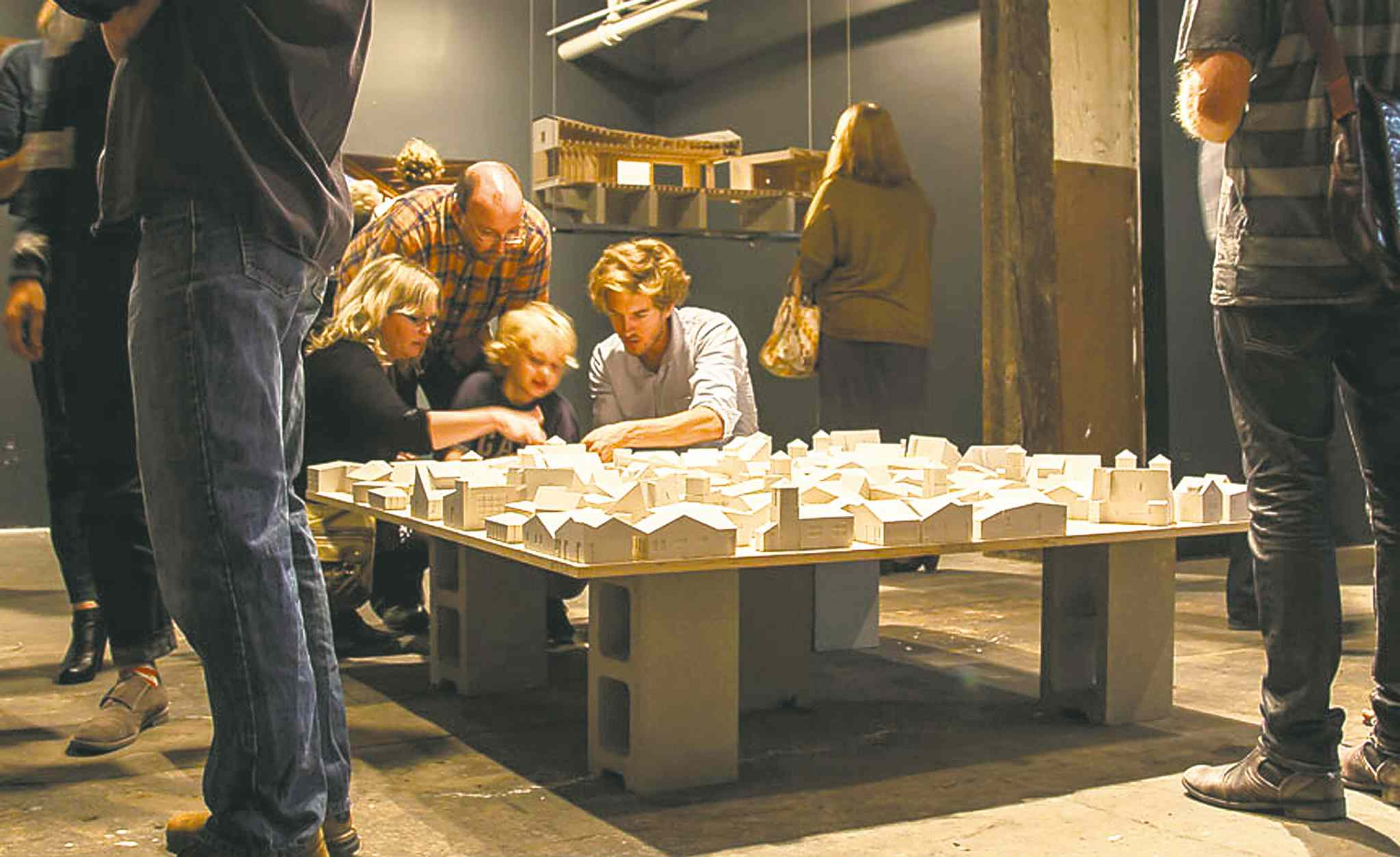 Visitors explore the plaster building forms in the centre of the gallery.