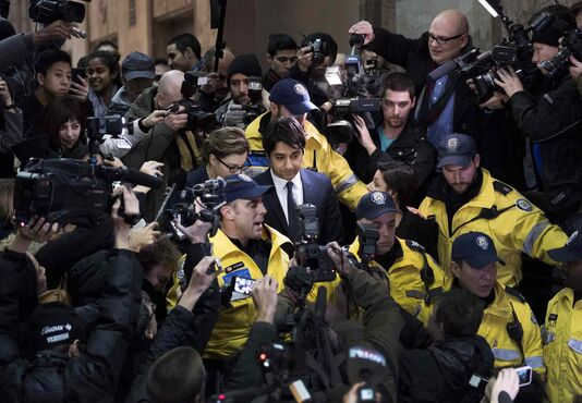 Former CBC Radio host Jian Ghomeshi (centre) is escorted out of court after being released on bail in Toronto on Wednesday. The 47-year-old turned himself in to police earlier today and was charged with four counts of sexual assault and one count of what police called