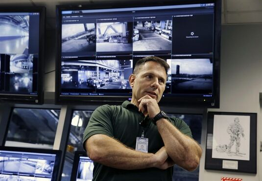 In this Oct. 15, 2014, photo, Daniel DeLorenzi, director of security and safety services at MetLife Stadium, stands near monitors for security cameras in the command center at the stadium in East Rutherford, N.J.