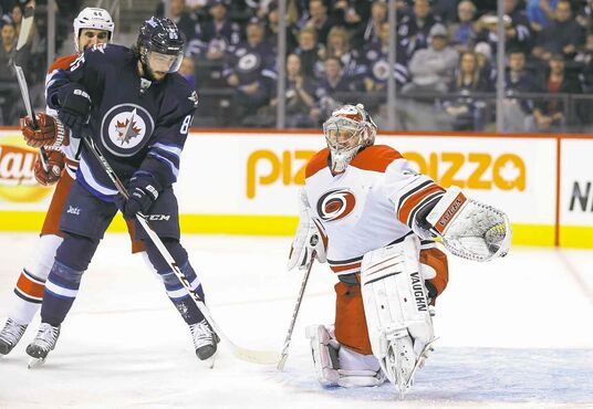 Jets' Mathieu Perreault watches Hurricanes goalie Anton Khudobin make the save.