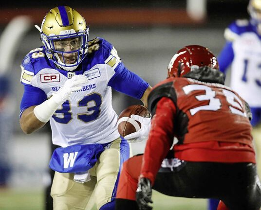 Winnipeg Blue Bombers' Andrew Harris, left, looks to get past Calgary Stampeders' Shaquille Richardson during first quarter CFL football action in Calgary on Nov. 3, 2017. Andrew Harris pointed to a couple of reasons why he captured his first CFL rushing title and set a league record for receptions by a running back.It was the extra, little things the Blue Bombers running back did during practices, plus the special bond he formed with the offensive line. THE CANADIAN PRESS/Jeff McIntosh
