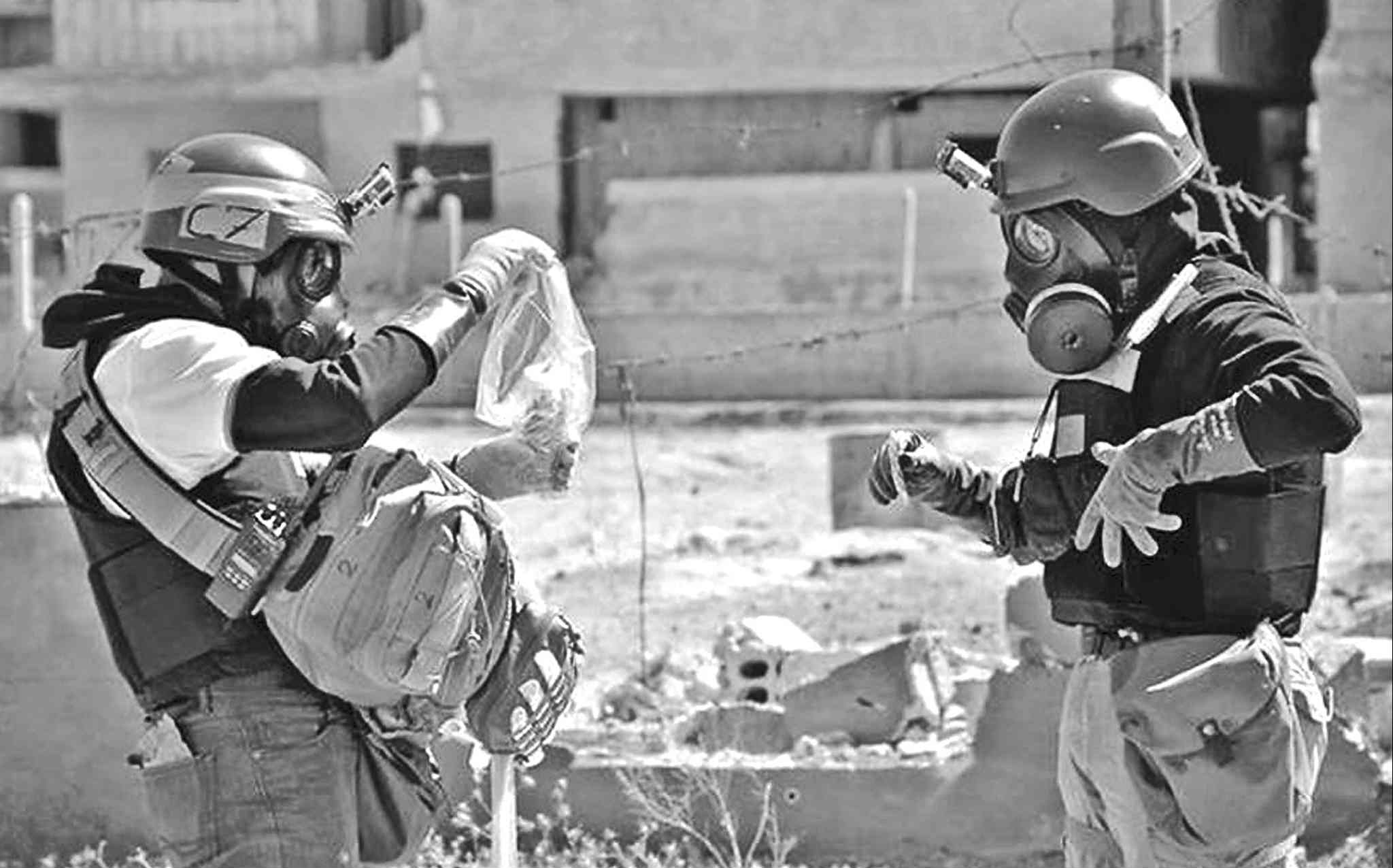 Members of a chemical-weapons investigation team take samples from the site of a chemical-weapons attack in Syria.