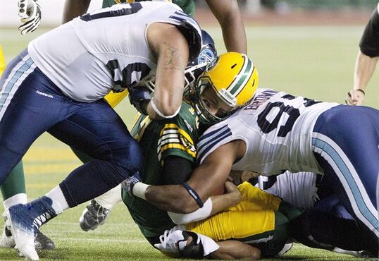 Toronto Argonauts' Cleyon Laing (90) and Ivan Brown (97) hit Edmonton Eskimos quarterback Mike Reilly (13) during first half action in Edmonton, Alta., on Saturday September 28, 2013. Reilly sustained a helmet-to-helmet hit on this play and was diagnosed with a concussion. A coalition of health and sporting groups across the country is calling for Canada's athletic organizations to get more proactive about protecting participants from head injuries. THE CANADIAN PRESS/Jason Franson.