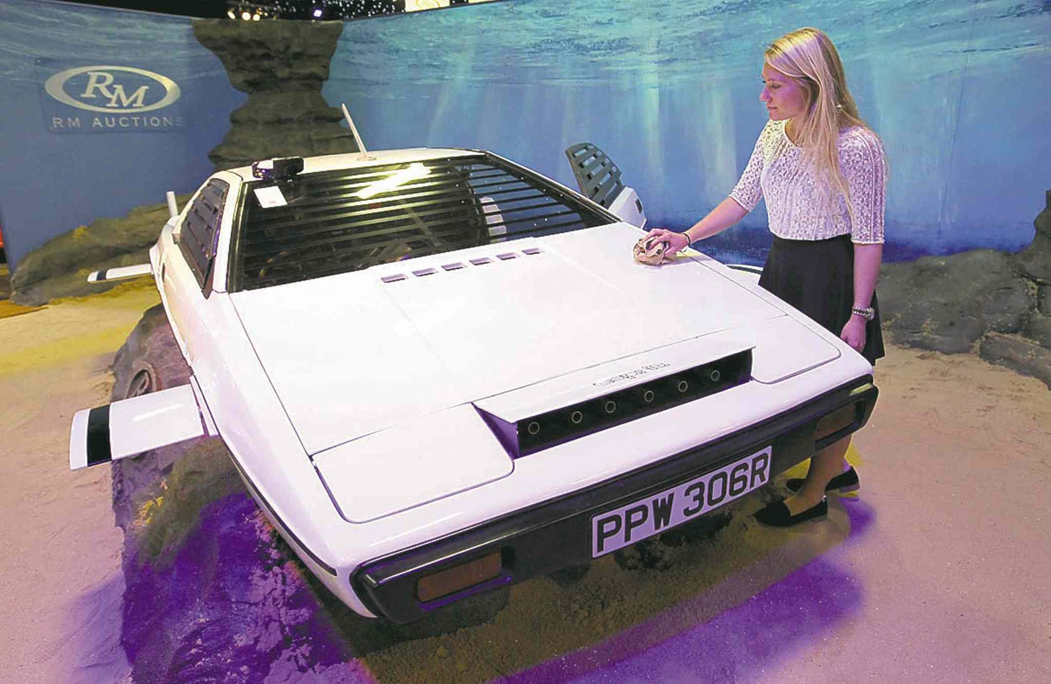 RM Auctions assistant Hannah Fairclough with the white Lotus Esprit used in the James Bond movie 'The Spy Who Loved Me'. The car was sold on Sept. 9  for 550,000 pounds ($865,000).