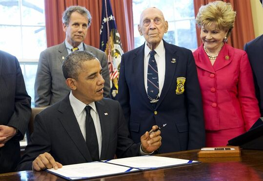 FILE - In this May 23, 2014 file photo, President Barack Obama, front left, signs H.R. 1209 in the Oval Office of the White House in Washington, next to Air Force Lt. Col. (ret.) Richard Cole, of Dayton, Ohio. H.R. 1209 awards a Congressional Gold Medal to the World War II members of the Doolittle Tokyo Raiders in recognition of their military service and 1942 raid on mainland Japan. From back left are Sen. Sherrod Brown, D-Ohio, Cole, and Rep. Madeleine Bordallo, G-Guam. (AP Photo/Jacquelyn Martin, File)