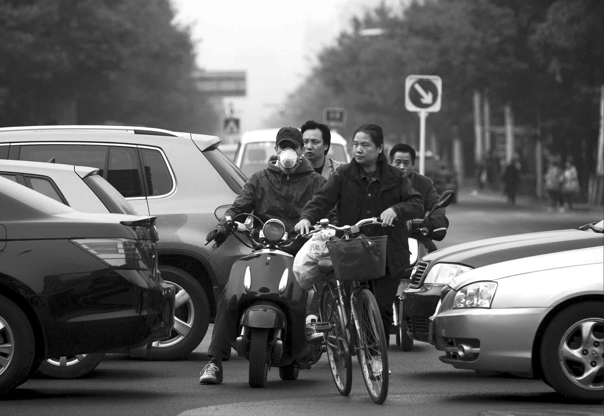 Bicyclists jostle with motorists on a polluted day in Beijing on Oct. 22.