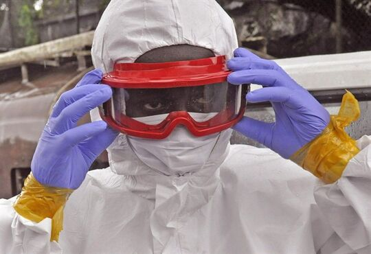 A Liberian health worker prepares his Ebola protective gear before removing the body of a man that they believe died from the Ebola virus in Monrovia, Liberia, Friday, Aug. 29, 2014. THE CANADIAN PRESS/AP-Abbas Dulleh