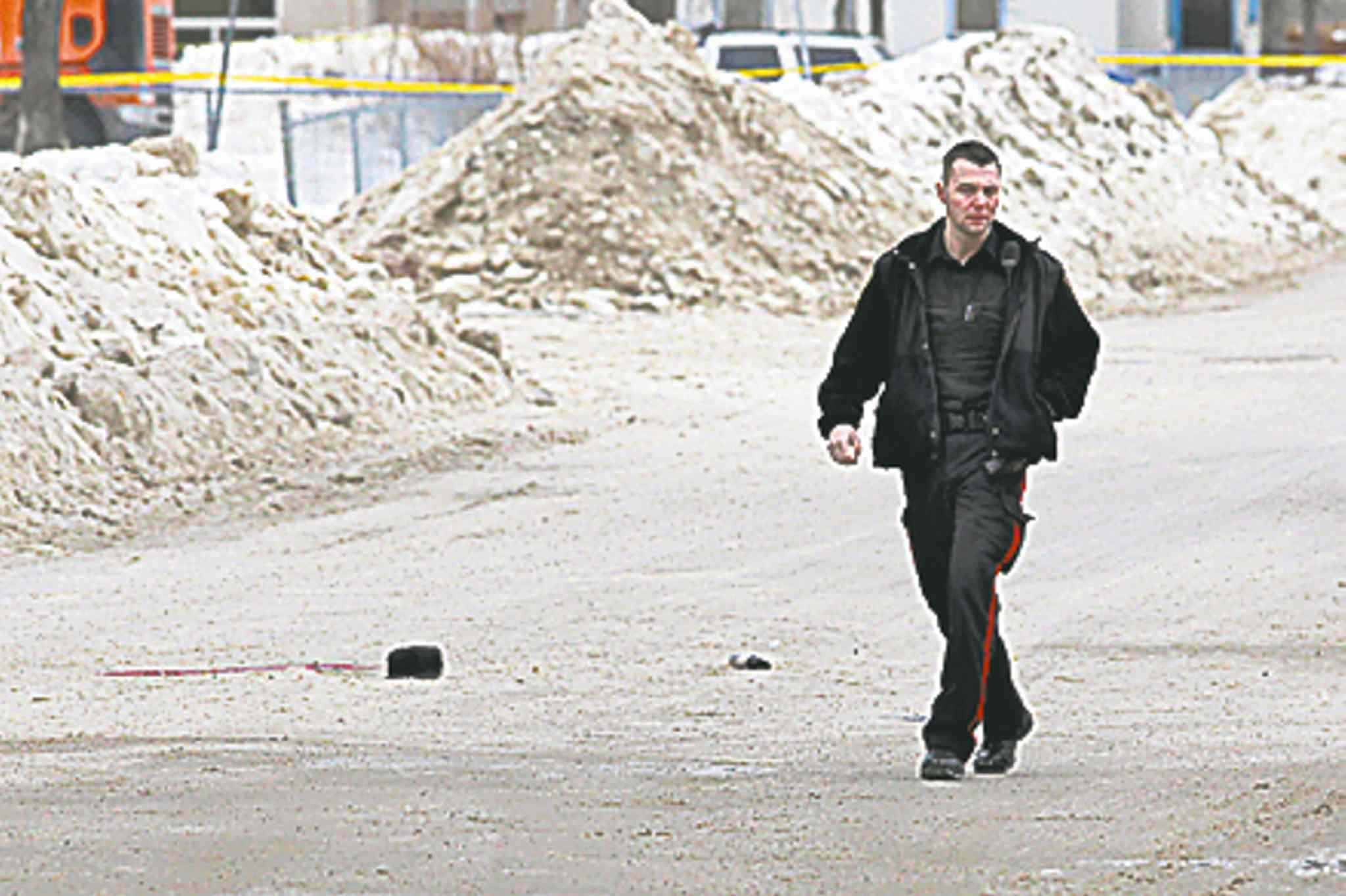 A police officer examines the scene of the shooting.