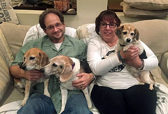 In this Dec. 5, 2014 photo provided by Michael Levitt, Jeff & Andee Dekofsky pose with their newly-adopted dog Bubbles, right, a 13-year-old dog seen in the