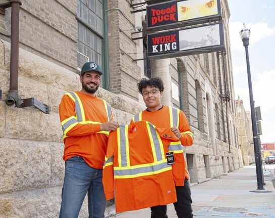 Artist Isaiah Binns (right) with the logo he designed on a shirt, with his former graphic-design teacher from Elmwood High School, Mathew Reis. (Mike Sudoma / Winnipeg Free Press)</p>