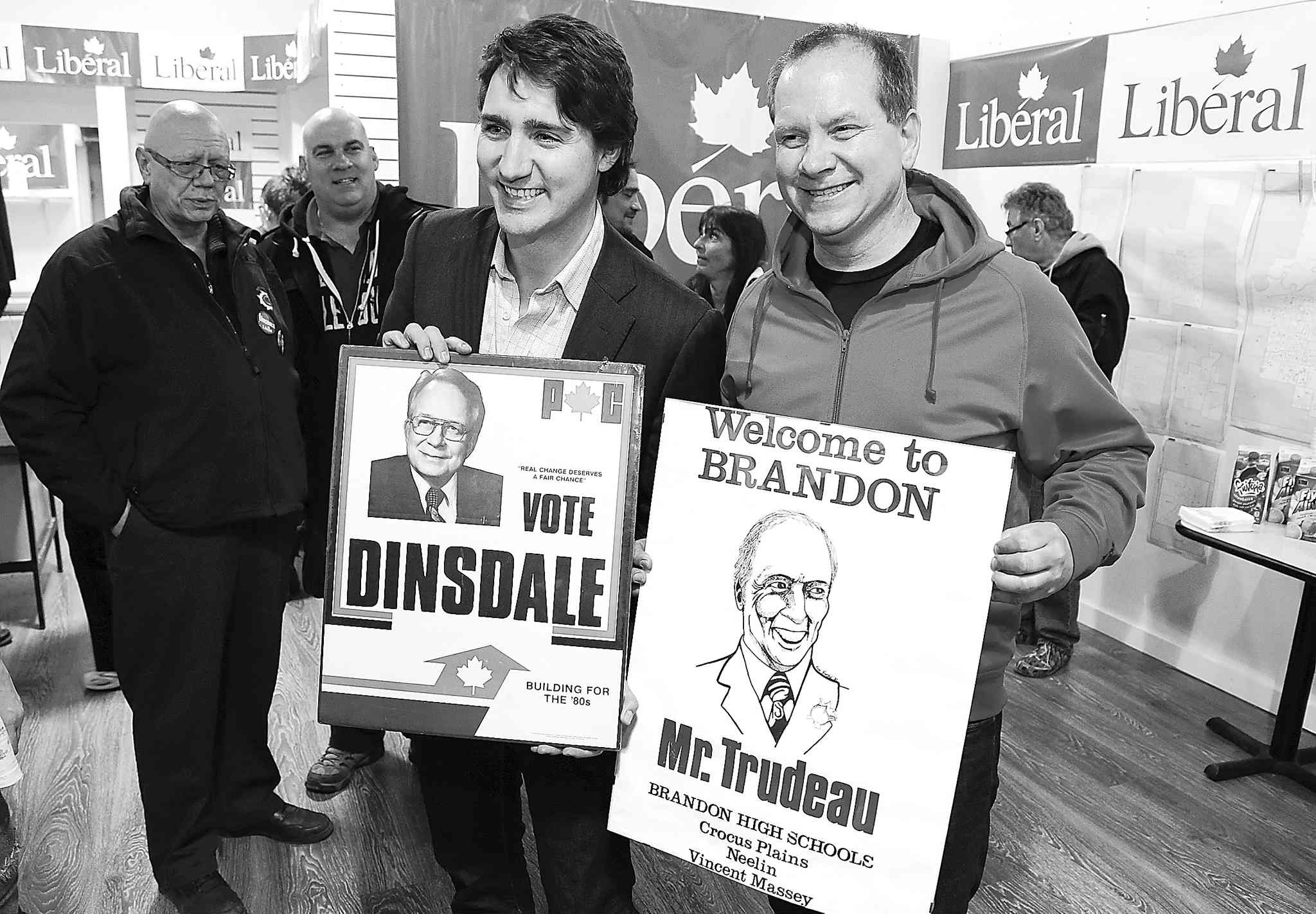 Federal Liberal Leader Justin Trudeau and candidate Rolf Dinsdale hold old posters of their politician fathers. Dinsdale believes he can steal the traditional Tory riding away from the Harper government.