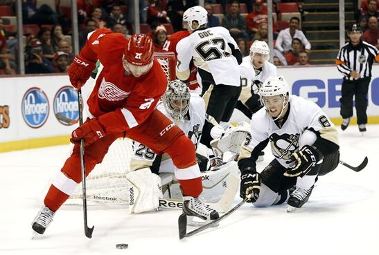 Pittsburgh Penguins defenseman Scott Harrington (6) defends Detroit Red Wings' Tomas Tatar (21), of Slovakia, in the second period of a NHL preseason hockey game in Detroit Wednesday, Oct. 1, 2014. (AP Photo/Paul Sancya)