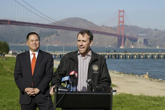 State assembly members Phil Ting, left, and Marc Levine, at podium, speak out against sidewalk tolls with the Golden Gate Bridge in the background during a press conference at Crissy Field Tuesday, Nov. 25, 2014, in San Francisco. The assembly members announced legislation to prevent the Golden Gate Bridge Highway and Transportation District from assessing a sidewalk toll on pedestrians and cyclists crossing the bridge. (AP Photo/Eric Risberg)