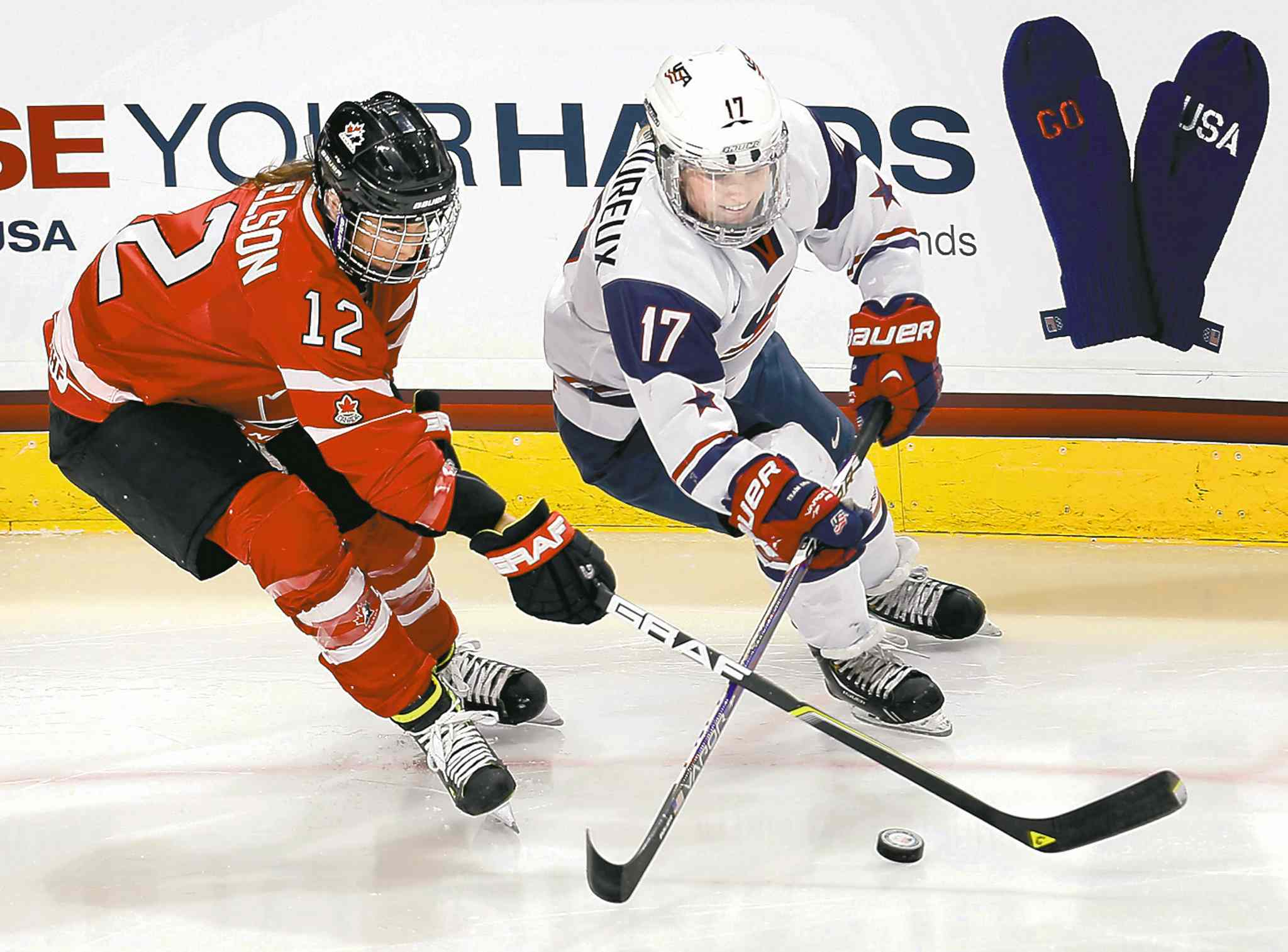 Canada's Meaghan Mikkelson (12) and Team USA's Jocelyne Lamoureux fight for the puck Saturday.