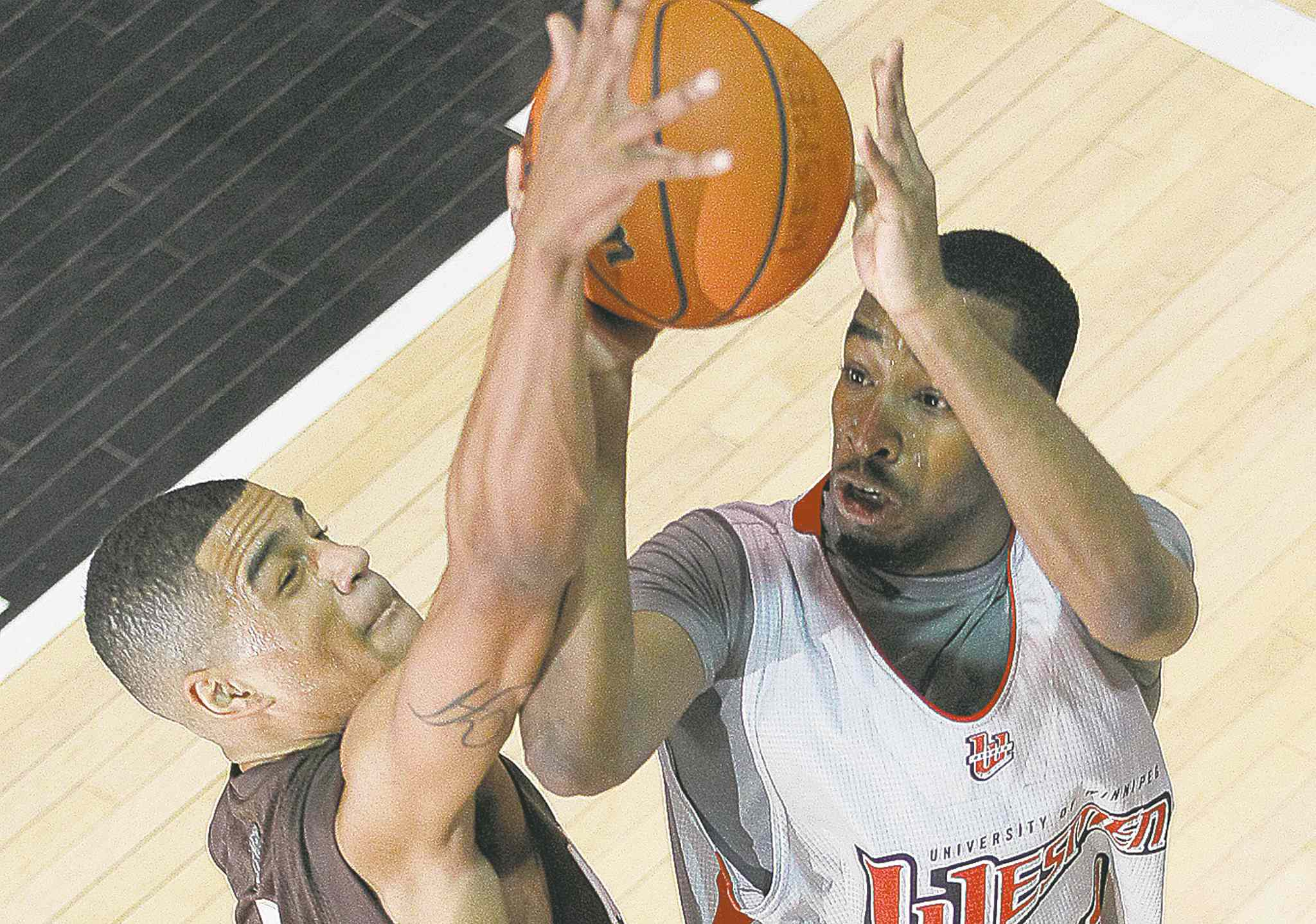 Wesmen Jordan Clennon (right) attempts to shoot over Bison Justus Alleyn during semifinal action at the Wesmen Classic.
