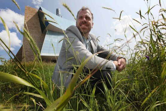 Landscape expert Bob Somers crouches in tall grass around the human rights museum. The intent is to get 'as close to a tall grass prairie here as one can,' he says.