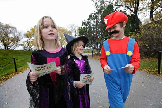 Dressed up as a witch, five-year-old Taylor McKenzie (middle) laughs with sister Katie (left) and Jonah