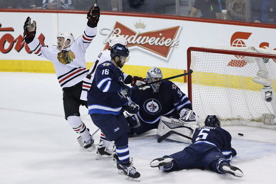 Chicago Blackhawks' Andrew Shaw (65) celebrates a goal against Winnipeg Jets goaltender Ondrej Pavelec (31) as Jets' Andrew Ladd (16) and Mark Stuart (5) defend and Hawks' Marian Hossa (81) looks on.