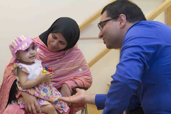 Dr. Aneal Khan, who led the team performing the liver-cell transplants, visits with Nazdana and her mom.