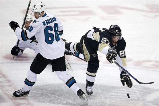 Pittsburgh Penguins' Sidney Crosby (87) collides at mid-ice with San Jose Sharks' Melker Karlsson (68) during the first period of an NHL hockey game in Pittsburgh, Sunday, March 29, 2015. (AP Photo/Gene J. Puskar)