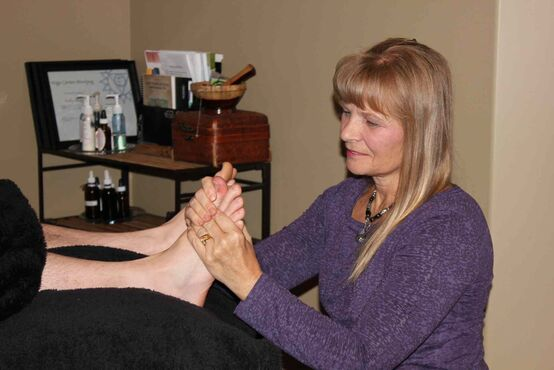 Licensed reflexologist Holly Allegro works on a client's foot and applies pressure on specific areas that are thought to relate to the body's organs and systems.