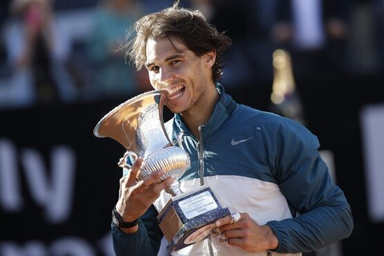 Spain's Rafael Nadal bites the trophy as he poses for photographers after defeating Switzerland's Roger Federer at the final match of the Italian Open tennis tournament in Rome, Sunday, May 19, 2013. Nadal won 6-1, 6-3. (AP Photo/Andrew Medichini)
