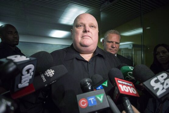 Toronto's outgoing mayor Rob Ford, left, stands next to his brother Doug Ford outside his office as he scrums with the media in Toronto on November 21, 2014. Former mayor Ford says his radiation treatments for a rare form of abdominal cancer are ending Thursday and he will know soon if doctors can operate. THE CANADIAN PRESS/Chris Young