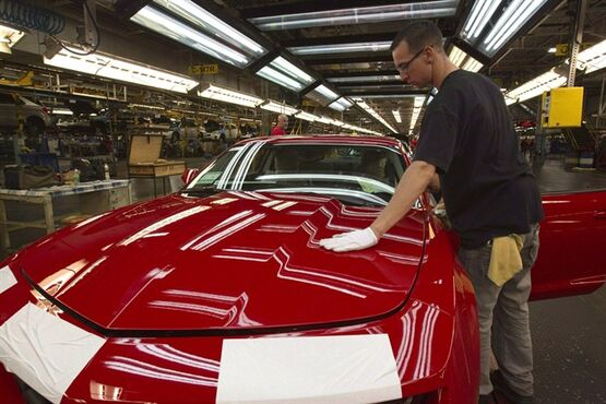 A worker checks the paint on a Camaro at the General Motors plant in Oshawa, Ont., June 10, 2011 The union representing auto workers at General Motors' Oshawa, Ont., plant says the company must decide now what will happen to its operations there instead of waiting until after the next contract negotiations.THE CANADIAN PRESS/Frank Gunn
