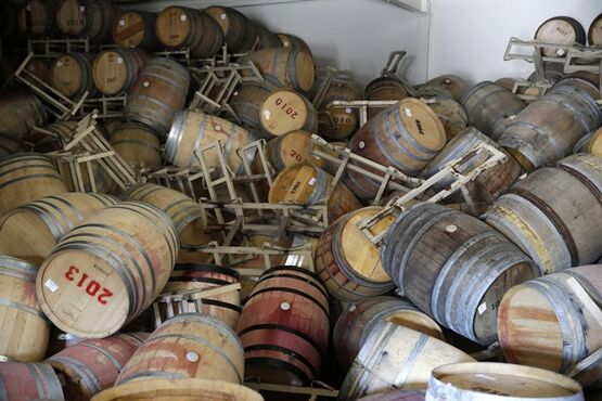 File - This Aug. 24, 2014 file photo shows barrels filled with Cabernet Sauvignon that toppled on one another following an earthquake at the B.R. Cohn Winery barrel storage facility in Napa, Calif. Napa Valley's seismically reinforced winery buildings generally held up to the largest earthquake to hit Northern California in a quarter-century, but the precious wine piled inside often did not. (AP Photo/Eric Risberg, file)