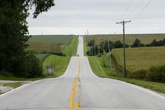In this Wednesday, Sept. 10, 2014 photo, a road lies between fields of corn and soybeans in Springfield, Neb. The nation's corn and soybean farmers will bring in by far the largest harvest ever this year, the U.S. Department of Agriculture said Thursday, Sept. 11, 2014. (AP Photo/Nati Harnik)