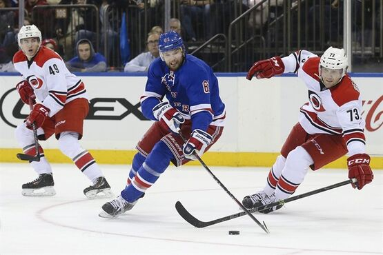 New York Rangers left wing Rick Nash (61) battles for the puck against Carolina Hurricanes defenseman Brett Bellemore (73) as center Victor Rask (49) looks on in the second period of an NHL hockey game, Sunday, Dec. 21, 2014, in New York. (AP Photo/John Minchillo)