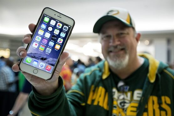 FILE - In this Sept. 19, 2014 file photo, John Mihalkovic, of Virginia Beach, Va., shows off his newly purchased iPhone 6 Plus outside the Apple store at Lynnhaven Mall in Virginia Beach. Apple's biggest new iPhone is selling for $100 more than its other new model, for a screen that is eight tenths of an inch larger. But a new report says it only costs Apples $15.50 more for the materials and manufacturing costs. (AP Photo/The Virginian-Pilot, The' N. Pham, File) MAGS OUT
