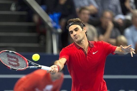 Switzerland's Roger Federer returns a ball to Croatia's Ivo Karlovic during their semifinal match at the Swiss Indoors tennis tournament in Basel, Switzerland, on Saturday, Oct. 25, 2014. (AP Photo/Keystone,Georgios Kefalas)
