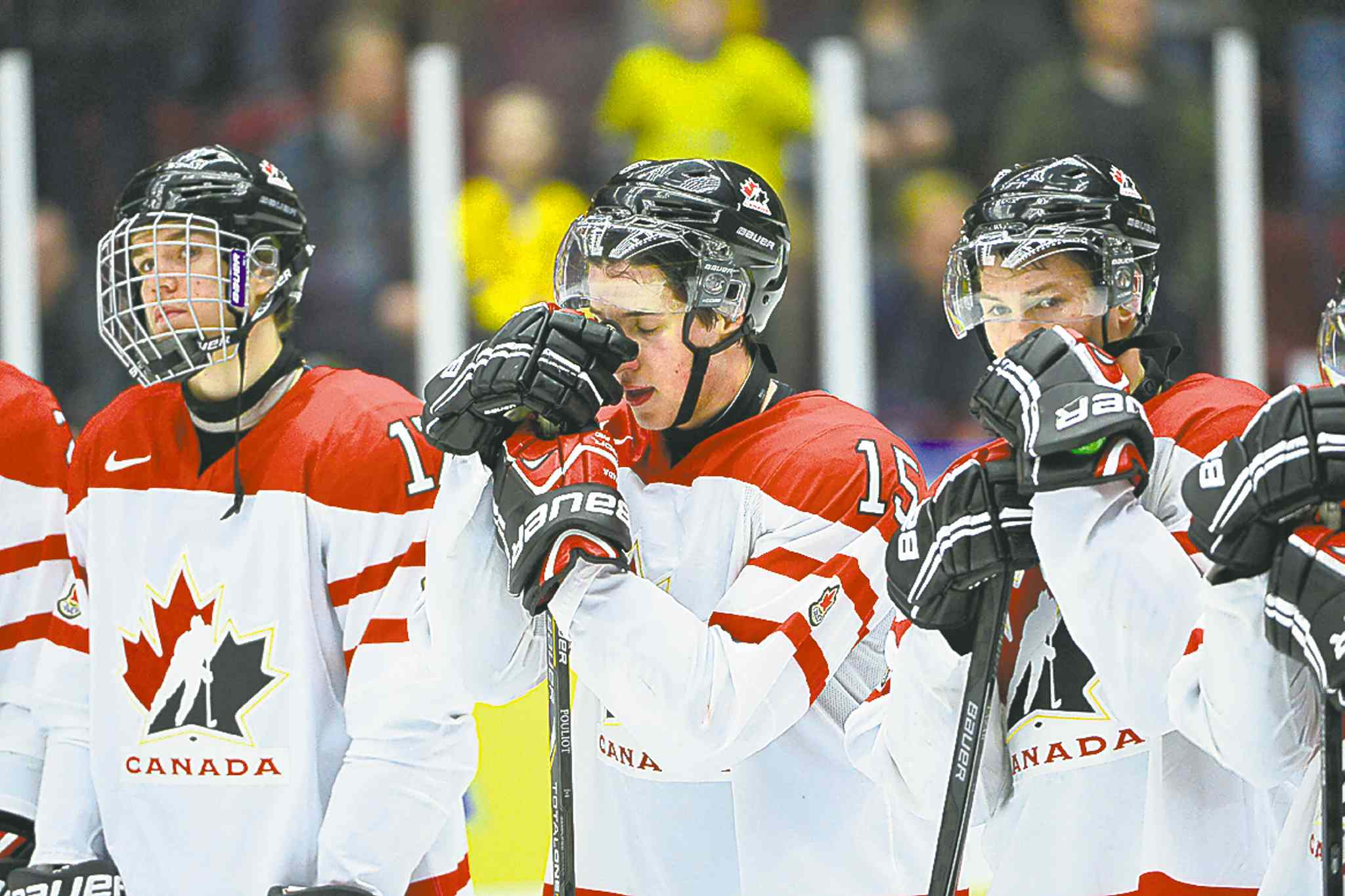 Team Canada defenceman Derrick Pouliot, centre, reacts after losing the bronze medal Sunday.