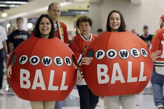 Brianwa Flores, left, and Katie Cosentino from Illinois State Lottery greet hockey fans before Game 2 of an NHL hockey playoff Western Conference semifinal between the Detroit Red Wings and the Chicago Blackhawks in Chicago, Saturday, May 18, 2013. A little more than a year after three tickets split a world-record lottery prize, the jackpot for Saturday's Powerball drawing was nearing historic territory. Should nobody pick the correct six numbers, the prize money will roll over to next week's drawing and almost certainly eclipse the $656 million doled out to winners in Illinois, Kansas and Maryland in the Mega Millions game in March 2012.