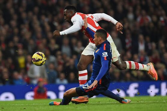 Arsenal's Danny Welbeck, top, and Manchester United's Chris Smalling compete for the ball during the English Premier League soccer match between Arsenal and Manchester United at the Emirates Stadium, London, Saturday, Nov. 22, 2014. (AP Photo/Tim Ireland)