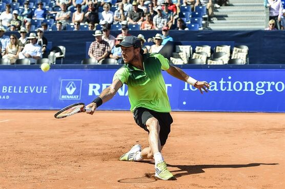 Juan Monaco of Argentina returns a ball to Thomaz Bellucci of Brazil during the quarterfinal match at the Suisse Open tennis tournament in Gstaad, Switzerland, Friday, July 25, 2014. (AP Photo/Keystone,Peter Schneider)