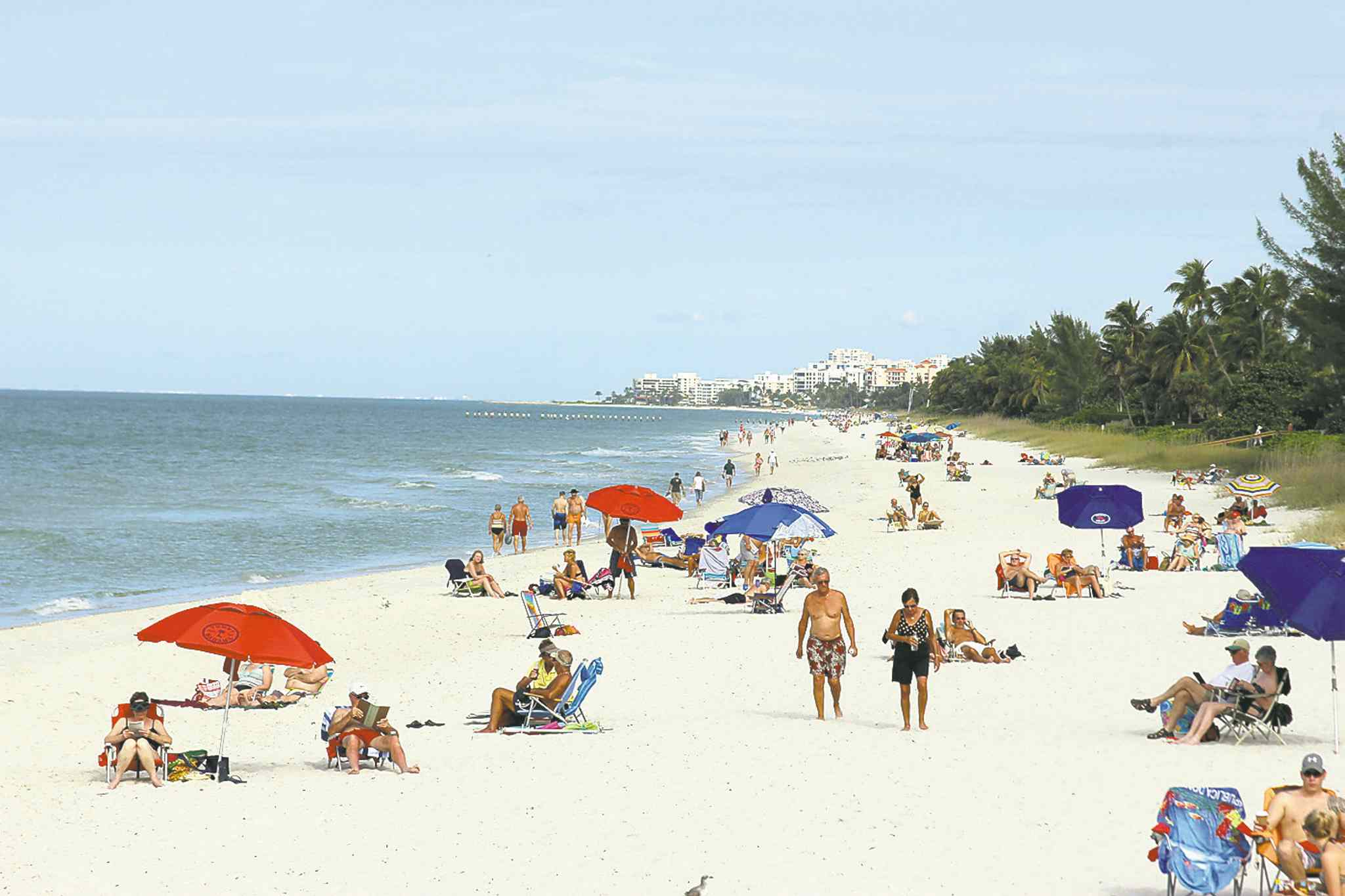 Beachgoers enjoy the sand and surf in Naples, Florida.