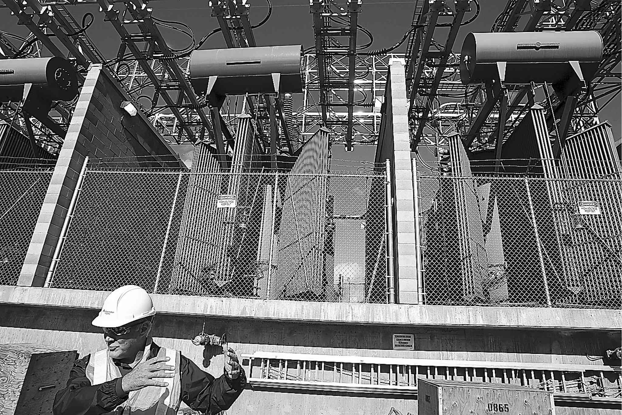 A Manitoba Hydro official stands beneath transformers at the Pointe du Bois generating station.
