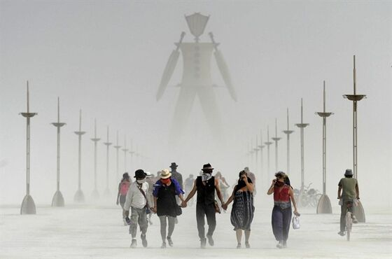 Burning Man participants walk through dust at the annual Burning Man event on the Black Rock Desert of Gerlach, Nev., on Friday, Aug. 29, 2014. Organizers call Burning Man the largest outdoor arts festival in North America, with its drum circles, decorated art cars, guerrilla theatrics and colorful theme camps. (AP Photo/The Reno Gazette-Journal, Andy Barron)