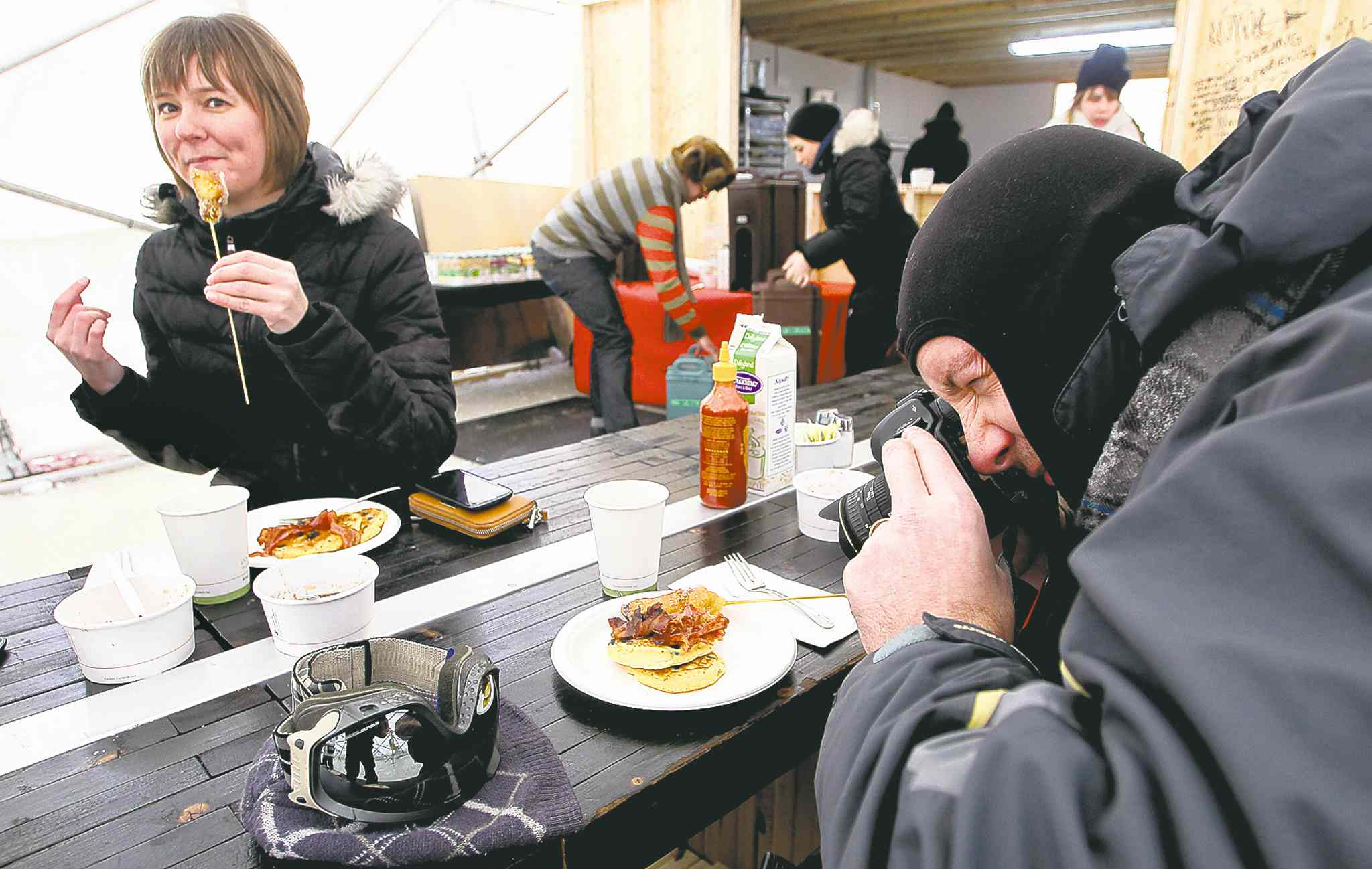 Brent Lelond takes a photo of his brunch at the Raw: Almond pop-up restaurant on the river ice at The Forks on Sunday as another customer enjoys her food.