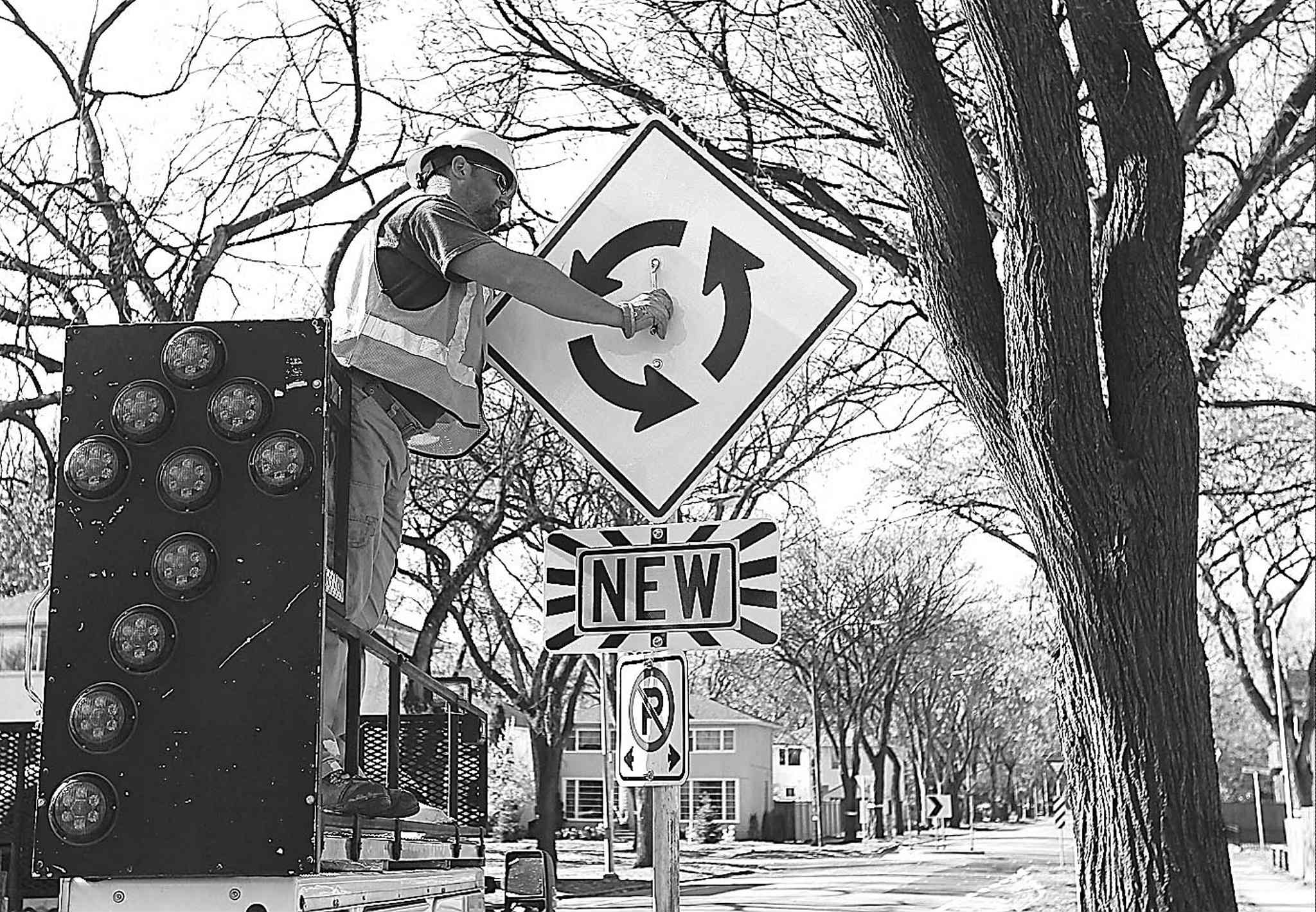 A city worker installs a sign near a traffic-calming circle on Grosvenor Avenue.