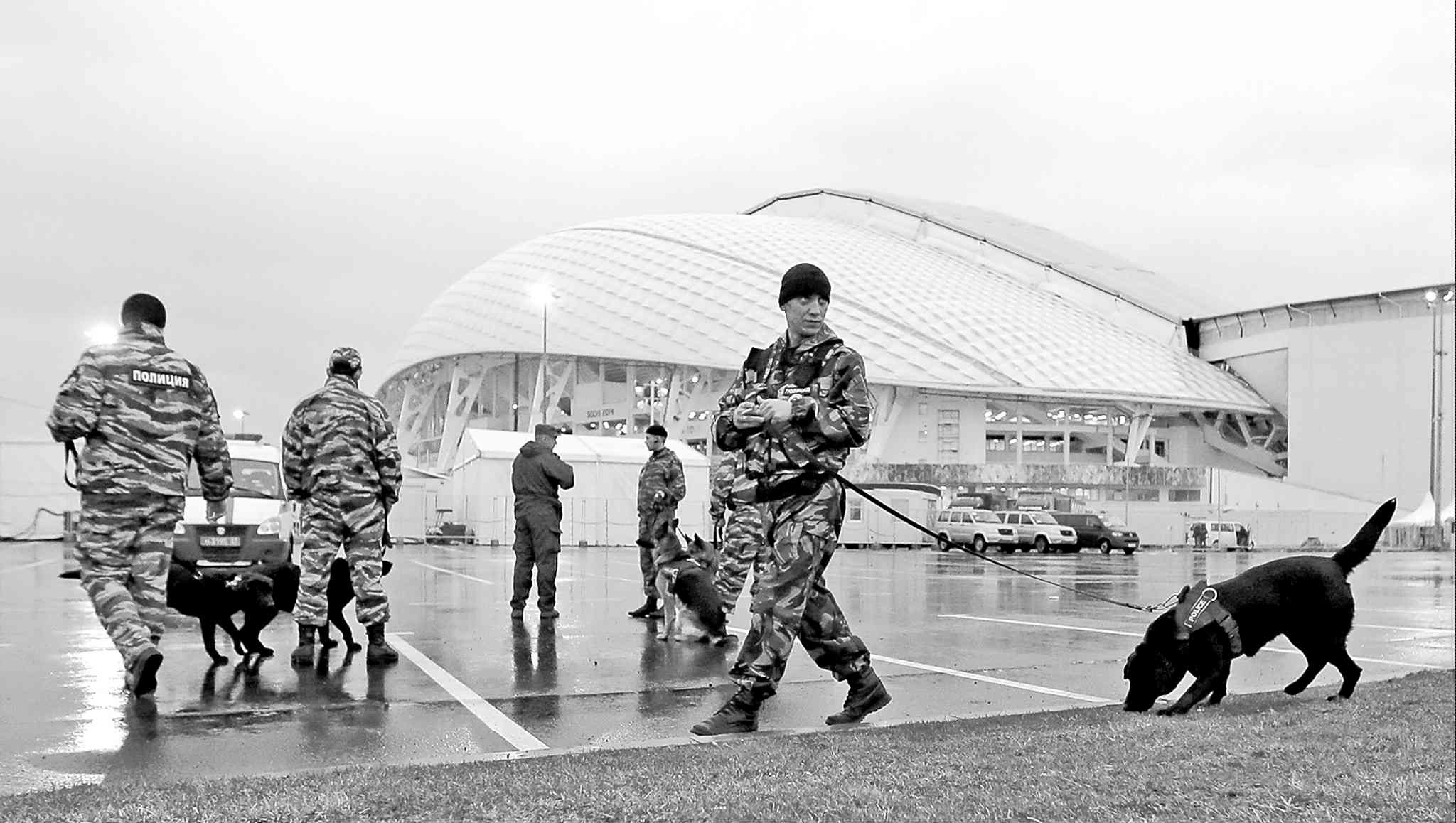 Security personnel and their dogs patrol Monday outside the Fisht Stadium in Sochi. The threat of terrorist attacks hangs over these Winter Games.