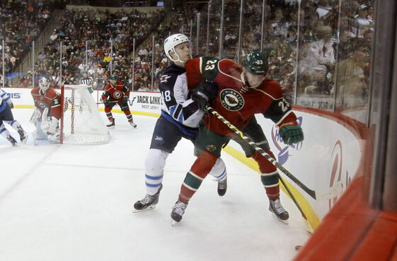 Winnipeg Jets' left wing Carl Klingberg (48) checks Minnesota Wild defenseman Gustav Olofsson (23) off the puck during the second period of Saturday's game in Saint Paul. Klingberg must clear NHL waivers before he can get to St. John's.