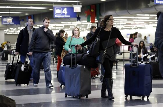 FILE - In this Dec. 1, 2013 file photo, travelers walk through terminal 3 baggage claim at O'Hare International airport in Chicago. The Department of Transportation on Monday, May 4, 2015 said that airline net income fell to $7.5 billion in 2014 from $12.2 billion in 2013. Airlines collected $3.5 billion in bag fees, a 5 percent increase over 2013. (AP Photo/Nam Y. Huh, File)