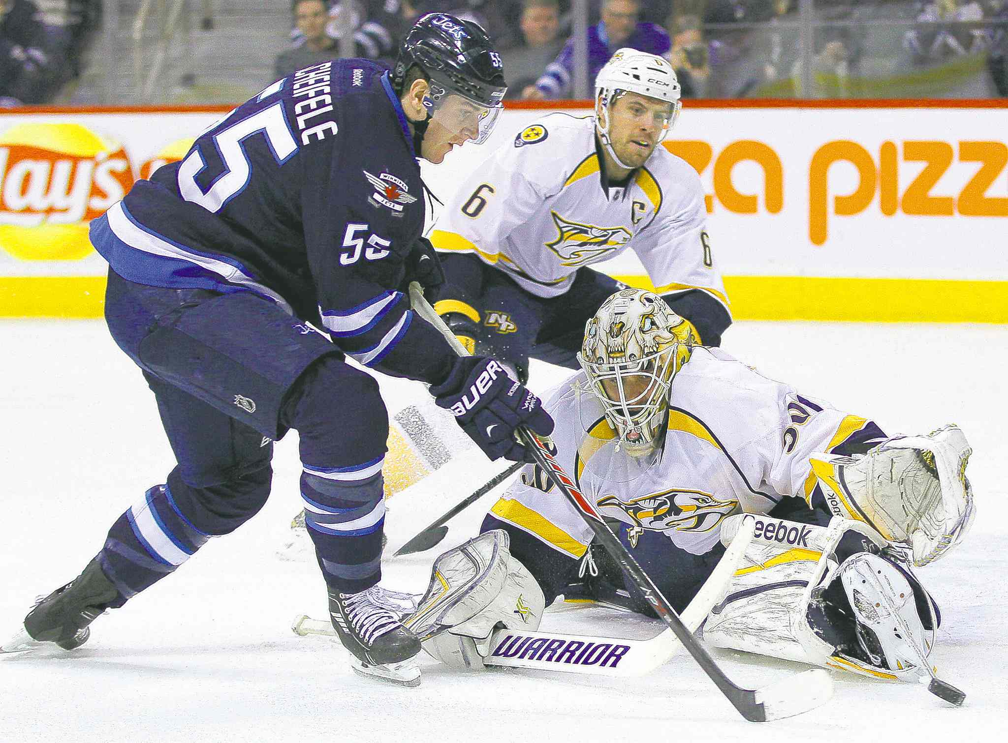 Jets' Mark Scheifele gets around Predators goaltender Carter Hutton before shooting the puck off Shea Weber for a goal.