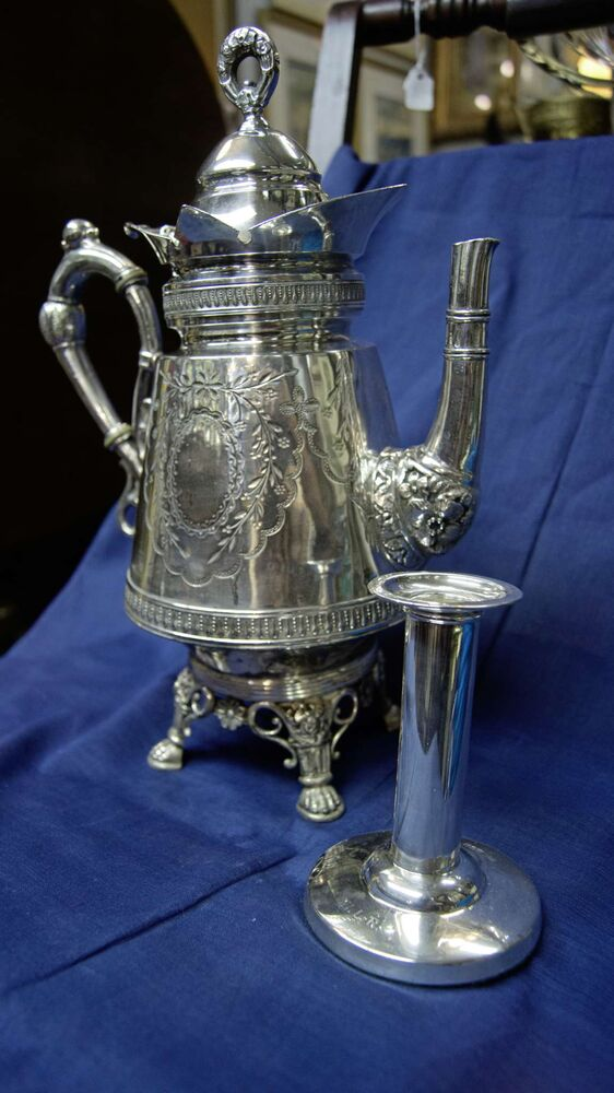 """What is your favourite piece? Silverware is one of Cooper's specialties. Identifying reactionary periods of silver work is one of his favourite pastimes.  Pictured: a mid-Victorian (1880s) serving jug (left) and a candle holder (circa 1915), both English in origin.  """"I love seeing contrast like that, and I can point that out to people. That's part of my teaching.""""  (Danielle Da Silva - Sou'wester)"""